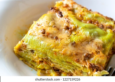 Typical italian dish green lasagna bolognesi on white plate and white table set. Closeup