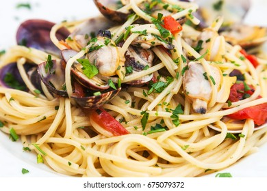 typical italian food - spaghetti alle vongole (spagetti with vongole clams venerupis mollusk) on plate close up in sicilian restaurant