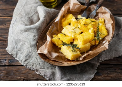 Typical Italian fried polenta with rosemary, selective focus