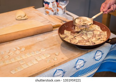 Typical Italian homemade agnolotti with stew ragù, uncooked fresh pasta and a rolling pin on a wooden cutting board