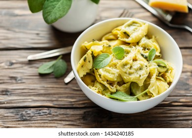 Typical italian pasta raviolli with sage and ricotta, rstic style and selective focus
