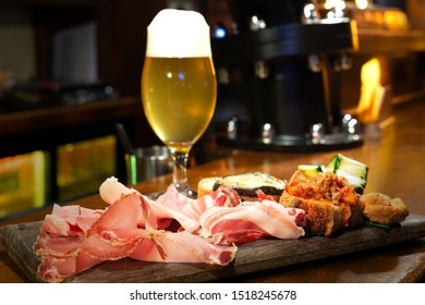 Typical Italian salami, cheese and vegetable platter: ham, salami, aubergine, courgette, bread, meat and tomato. Glass of beer in the background, focus on the foreground. Rustic catering.
