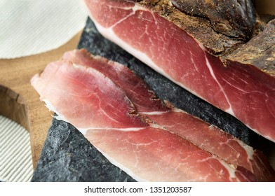 Typical Italian smoked Speck with two slices on a slate plate on wooden cutting board