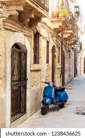 Typical Italian street with blue scooter