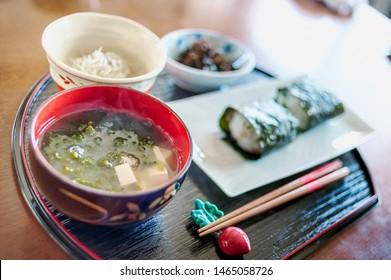 Typical Japanese breakfast served with onigiri rice balls, seaweed, miso soup and fish.