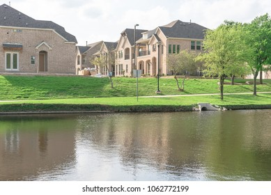 Typical lakeside new-established community with newly built detached single-family homes. Cloud blue sky reflection near urban park with walking path in suburban Irving, Texas, USA