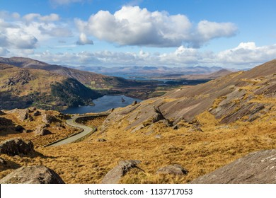 Typical landscape from Ireland. Amazing picturesque view of wonderful nature. Rocks, stones, mountains, cloudy sky, colorful. Very popular travel destination. Road leading to valley.