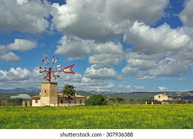 Typical landscape of Majorca with an ancient mediterranean windmill and clouds on the sky