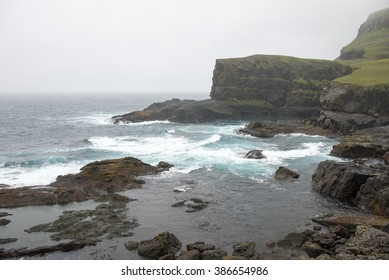 Typical landscape on the Faroe Islands, with rough coast on a rainy day in Hvalba