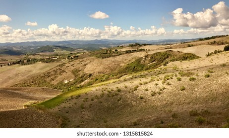 Typical landscape in Tuscany, Italy with winding roads, hills with cypress and pine trees and various fields with houses and small villages