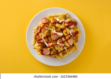 Typical Latin America Salchipapa on yellow background. Sausages with fries, ketchup,mayo and mustard.