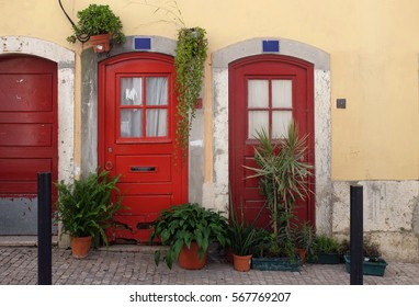 Typical Lisbon old red doors decorated with pots of plants in Bica Neighborhood