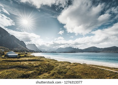 A typical Lofoten beach view frames the sea at Ramberg Lofoten. Scene on a beautiful day with blue sky and some clouds with grass in the foreground. Lofoten Islands, Norway Europe