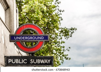 Typical London underground sign, in a cloudy day, United Kingdom