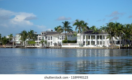 Typical luxury riverfront summer homes along quiet river in tropical southern location on beautiful summer day. Exterior generic establishing shot