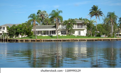 Typical luxury vacation summer home exterior establishing shot photo during day time. Generic large expensive real estate mansion along coastal waterway river