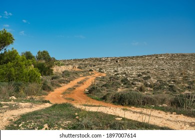 The typical maltese mediterranean countryside on a sunny day in late summer (autumn). View of a small and gravel road to the Coast on a sunny day. Hiking and vacation on the island of Malta, Europe.