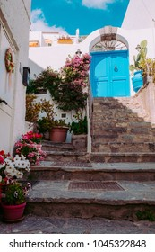Typical Mediterranean style island house entrance with flowers in pots and stairs.