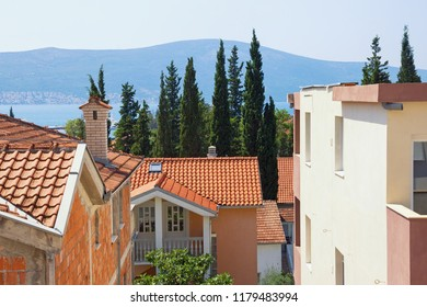 Typical Mediterranean urban landscape: houses with red tiled roofs ,  green cypresses.  Montenegro,  Bay of Kotor, Tivat town