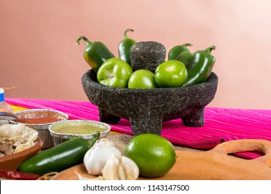 Typical Mexican food dishes with sauces on colorful table. Stone molcajete with chilies and green tomatoes