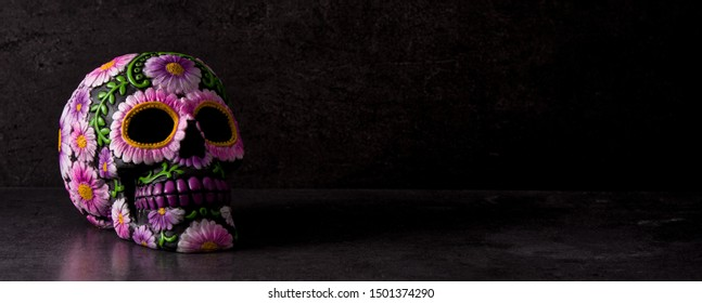 Typical Mexican skull painted on black background. Dia de los muertos. Panorama view
