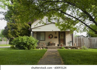A typical middle income modern day home with a green lawn.