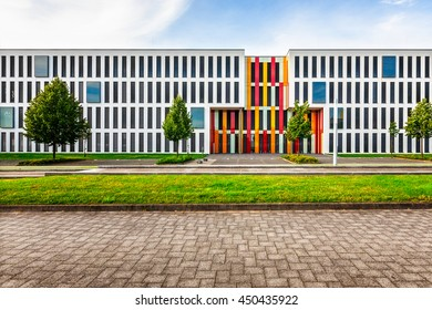 Typical modern new office or college school building exterior. Backyard with parking lots, lawn, trees and road