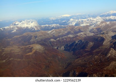 Typical Montenegrin landscape from above. Mountains of Montenegro include most rugged terrain in Europe. Moss covered plateau near bottomless gorge. The Balkans, aerial view. Background of snowy peaks