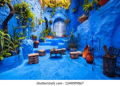 Typical moroccan courtyard in Chefchaouen blue city medina in Morocco with blue walls and decorated with various objects (pots, jugs)