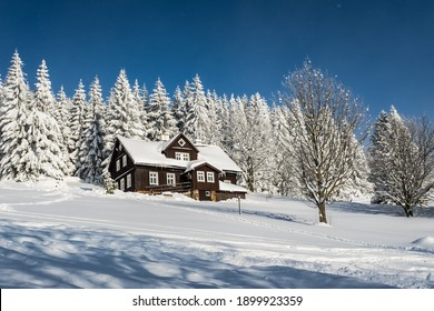 Typical mountain house after forest in the mountains, Czech Republic, Giant Mountains. Trees covered with snow on a sunny winter day. - Shutterstock ID 1899923359