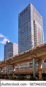 Typical multilevel roads in Tokyo with train, cars and skyscrapers nearby under blue cloudy sky in winter