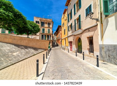 Typical narrow street among old houses in Old Town of Palma de Mallorca, Spain.