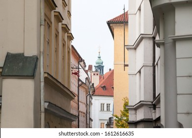 Typical narrow street of Stare Mesto, Michalska ulice, in the historical center of Prague, Czech Republic, with a focus on the top of the clock tower of a medieval baroque church.   - Shutterstock ID 1612616635