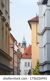 Typical narrow street of Stare Mesto, Michalska ulice, in the historical center of Prague, Czech Republic, with a focus on the top of the clock tower of a medieval baroque church.   - Shutterstock ID 1736226941