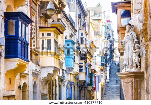 Typical narrow streets with colorful balconies in Valletta , Malta