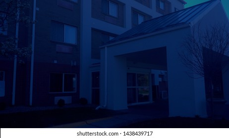 Typical night time exterior establishing shot close up of generic hotel lobby entrance. NX building facade view under awning.