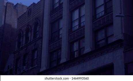 Typical night time exterior establishing shot of New York City style luxury apartment building and neighbor structures at dusk under moon light