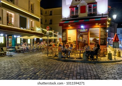 Typical night view of cozy street with tables of cafe in quarter Montmartre in Paris, France. Architecture and landmarks of Paris. Postcard of Paris