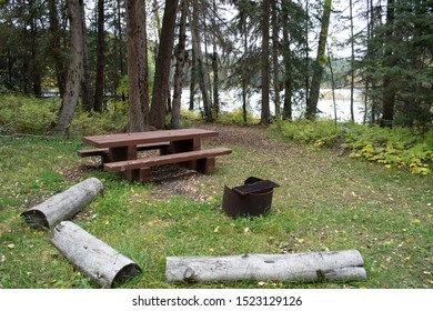 Typical north american rustic campsite with wooden picnic table and fire ring in the woods.
