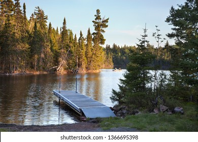 A typical northern Minnesota lake with a dock and fishermen in the distance
