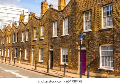 Typical old English buildings, low brick buildings across a narrow street, interesting old London architecture, english houses