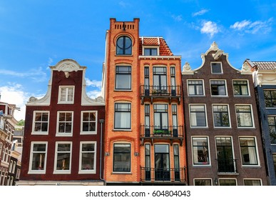 Typical old houses of Amsterdam, Netherlands under blue sky.