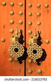 Typical old rustic studded wooden door with Islamic patterns on brass doorknockers, Morocco.