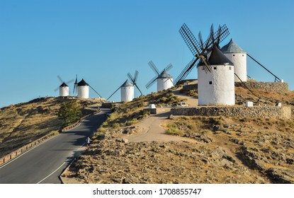 Typical old white Spanish windmills (Molinos appearing in Don Quijote) surrounded by a dry landscape in Consuegra, Toledo. Castilla la Mancha, Spain.