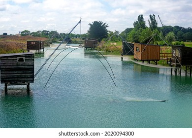 Typical old wooden fishing huts on stils of canal over water. French Atlantic coast. Vendee, France.. - Shutterstock ID 2020094300