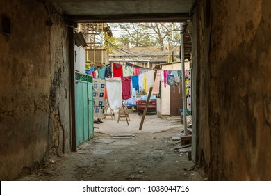 Typical old yard of a poor, beggar quarter. Underwear is dried on rope between old houses with old windows. Old town quarters with slums and dilapidated housing. Crisis, homeless social catastrophe