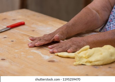 A typical orecchiette lady from the italian city Bari is kneading the dough on a wooden table to make pasta