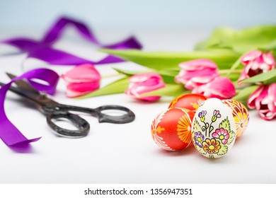 Typical painted easter egg from Slovakia with tulips, ribbon and scissors.