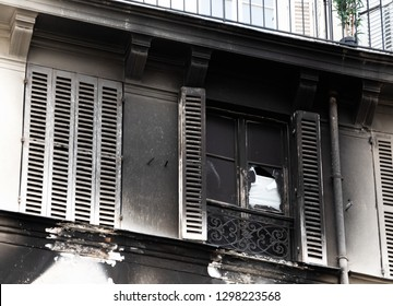 Typical Parisian building exterior after fire. Burnt charred wall. Temporary renovation. Paris, France. Real estate insurance importance concept.