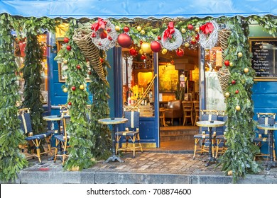 Typical Parisian cafes decorated for Christmas holidays in the artists' quarter Montmartre in Paris at winter morning, France